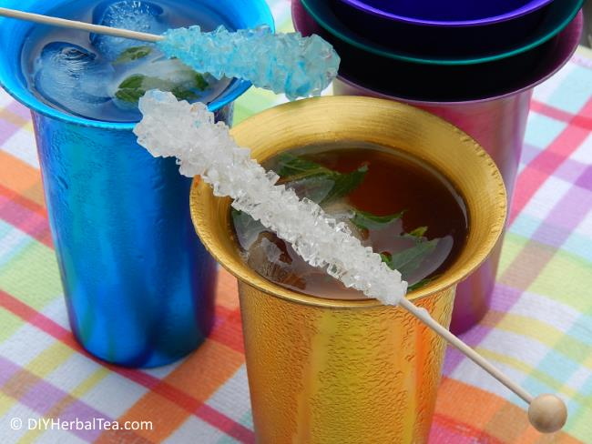 Herbal iced tea in colorful metal tumblers, and rock candy swizzle sticks