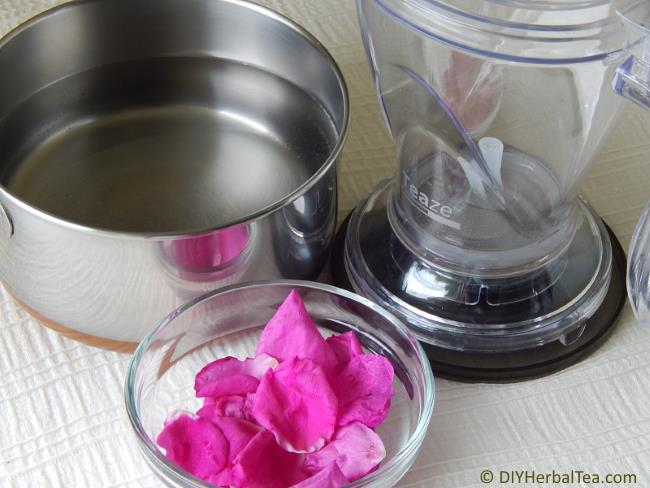 Kettle of water, tea infuser pot, and a dish of rose petals